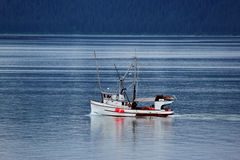 Small Trawler on Glacier Bay Alaska. Small trawler preparing for fishing near Glacier Bay National Park and Preserve, Alaska.  Calm blue sea, clouds and mountain Stock Photography