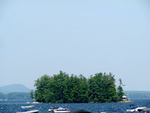 Small tree-covered island in Maine on a foggy day surrounded by boats Royalty Free Stock Image