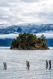 Small tree covered island. By snow caped mountain range Royalty Free Stock Photos