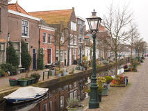 Small tree lined canal amidst residential housing Royalty Free Stock Image