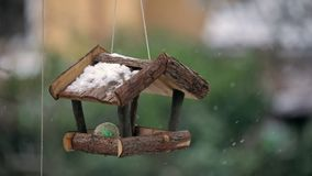 Small treehouse for the birds. In falling snow stock video