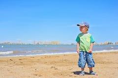 Small trendy boy standing sandy beach Royalty Free Stock Image