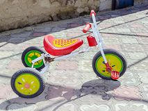 A small tricycle is in the yard stock photo
