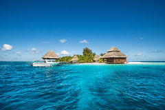 Small tropical island with Beach Villas and speed boat Stock Image