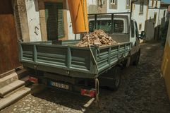 Small truck with dump full of rubble and house under refurbishment. Small truck with dump full of rubble next to old house under refurbishment, on sunny day at royalty free stock images