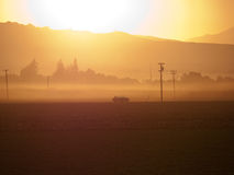 Small truck on a side road at sunrise. Farming area with perfectly flat land surrounded by small hills. Morning mist and fog with sun providing a yellow cast Stock Photography