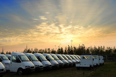 Small trucks in a parking lot under the setting sun Stock Image