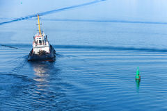 Small tug boat goes on a fairway Stock Images