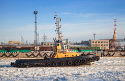 Small tug boat goes through icy channel Royalty Free Stock Image
