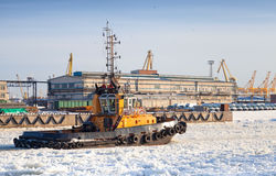 Small tug boat goes on icy channel Royalty Free Stock Image