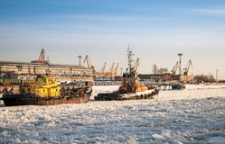 Small tug boat goes with vessel through ice Stock Image