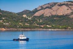 Small tug boat  underway on Porto-Vecchio bay Royalty Free Stock Photography