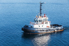Small tug boat with white superstructure. And dark blue hull underway on sea water Stock Photos