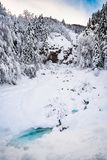 Small turquoise creek flows through snow covert winter wonderlan. D with forest in background Royalty Free Stock Photography