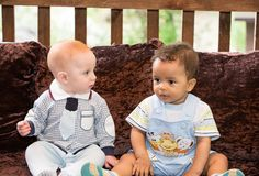 Small two children: black american and caucasian boys siting Royalty Free Stock Photos