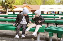 Small two children in warm caps playing in autumn city park on green bench stock photography