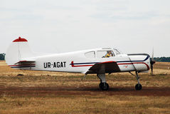 A small two-seater white airplane rides on the field Royalty Free Stock Images