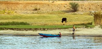 Small typical Egyptian boat stranded on the riverbank with an adult watching and a chil. Nile river, near Aswan, February 16, 2017: small typical Egyptian boat royalty free stock photos