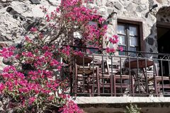Small typical terrace with flowers at the house in Pyrgos Stock Photos