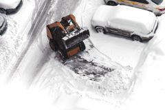 A small urban snow removal machine works in the courtyard of a residential building. View from above. Selective focus. A small urban snow removal machine works stock images