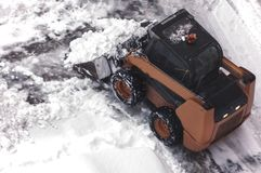 A small urban snow removal machine works in the courtyard of a residential building. View from above. Selective focus. A small urban snow removal machine works royalty free stock images