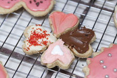 Small Valentine heart cookies pointing at each other on a cooling rack of different types of frosting and sprinkles. stock photo