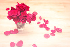 Small vase with red roses and petals Stock Photos