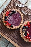 Small vegan tarts made of nuts and berry jam decorated with blac Stock Photography