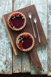 Small vegan tarts made of nuts and berry jam decorated with blac Stock Photo