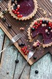 Small vegan tarts made of nuts and berry jam decorated with blac Stock Images