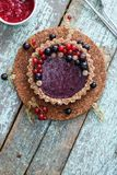 Small vegan tarts made of nuts and berry jam decorated with blac Royalty Free Stock Photo