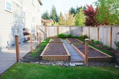 Small vegetable garden in the fenced back yard. Royalty Free Stock Photography