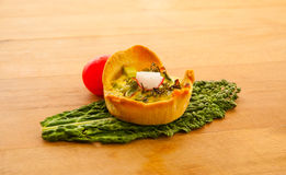 Small vegetable quiche tart on kale leaf Royalty Free Stock Image