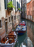 Small Venetian Canal. Motorboats parked near specific walls of houses on a small canal in Venice Stock Photography