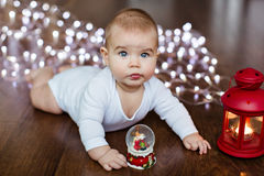 Small very cute baby lying on the wooden floor on the background royalty free stock photos