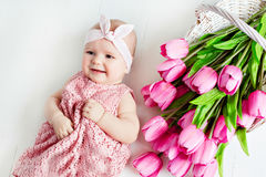 Small very cute, big-eyed little baby girl in a pink dress lying stock photography