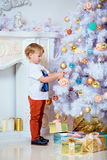 Small very cute blond boy hangs up the ball on a white Christmas Stock Photo