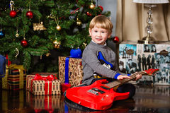 Small very cute blond boy holding red guitar on the background o. F the Christmas tree Royalty Free Stock Photo