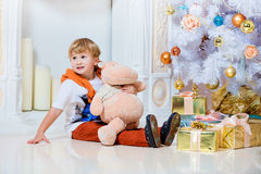 Small very cute blond boy sitting by the fireplace and white Chr Stock Image