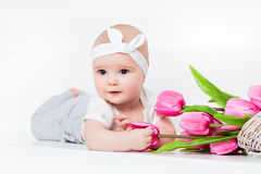 Small very cute wide-eyed smiling baby girl lying on her tummy o Royalty Free Stock Photo