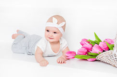 Small very cute wide-eyed smiling baby girl lying on her tummy o Stock Image