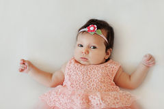 Small very cute wide-eyed smiling baby girl in a pink dress lying in  white blanket Stock Photos