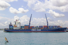 Small vessel and huge container ship, harbor of Stone Town Royalty Free Stock Photos