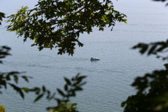 Small vessel seen through trees in Lake of Geneva, Switzerland, in hot sunny day in June Royalty Free Stock Image