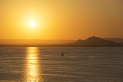 Small Vessel at Sunset in La Manga del Mar Menor. Small Vessel Sailing against Mountain Horizon at Sunset - La Manga, Mar Menor Side, Cabo de Palos, Cartagena royalty free stock images