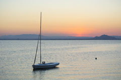 Small Vessel at Sunset in Mar Menor. Small Vessel, without Sail on Mast at Sunset - La Manga, Mar Menor Side, Cabo de Palos, Cartagena and San Javier, Murcia Royalty Free Stock Photos