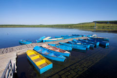 Small vessels arranged together in a lake, in the fall Stock Photo