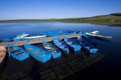 Small vessels arranged together in a lake, in the fall Stock Image