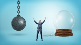 A small victorious businessman stands near a broken glass sphere and an iron wrecking ball. Business and success. Freedom for enterprise. Unrestricted business Royalty Free Stock Photo