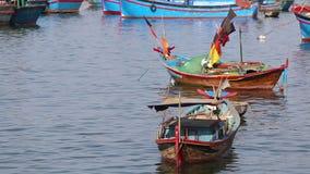 Small vietnamese fishing boats roll in sea bay at dawn. Small vietnamese fishing boats with colourful banners roll in sea bay at dawn stock video